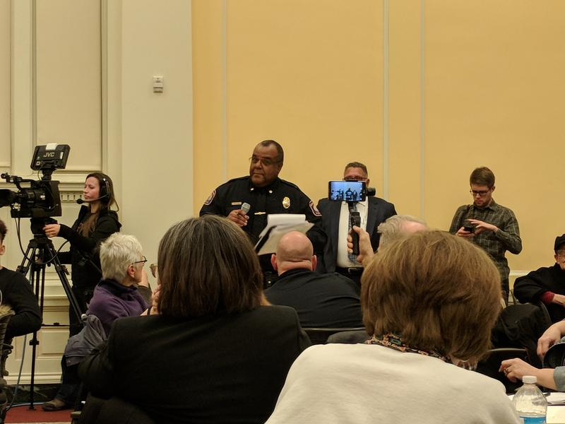 A Grand Rapids police officer standing at a table with a microphone