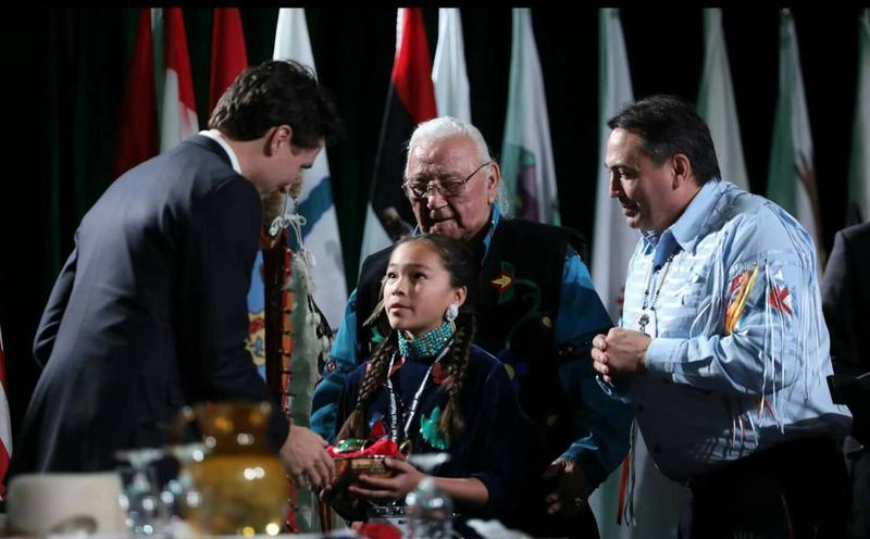 Autumn Peltier presenting Canadian Prime Minister Justin Trudeau with a gift from Assembly of First Nations Chiefs, December 2016.
