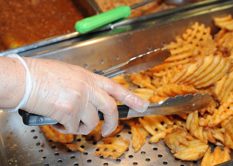 A cafeteria worker's gloved hand grabs waffle fries with tongs.