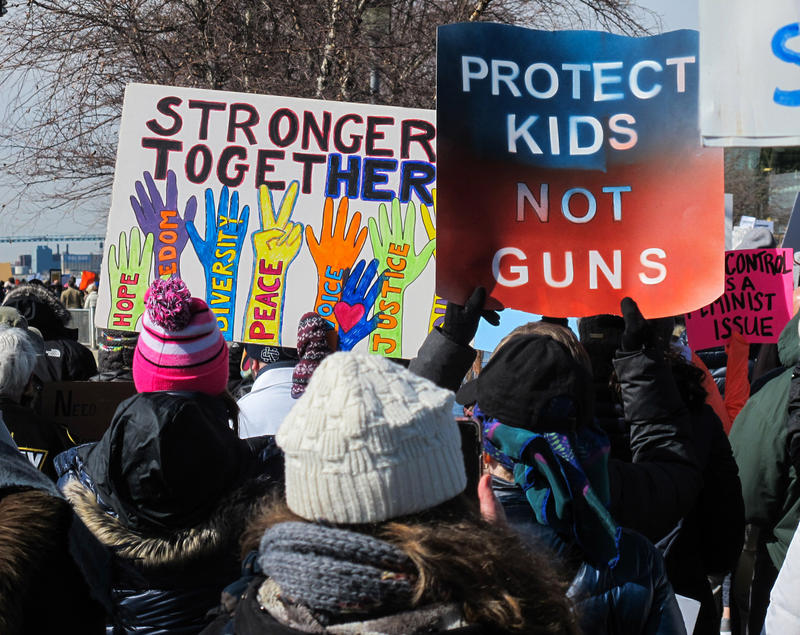 "Two signs side by side. One says ""Stronger Together"" and the other says ""Protect Kids Not Guns"""