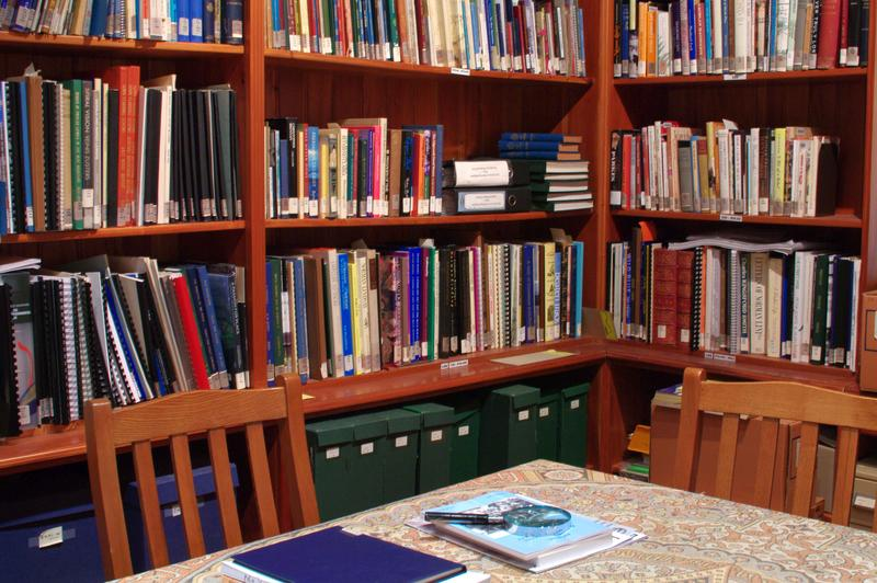 Corner of a library with bookshelves and a study table