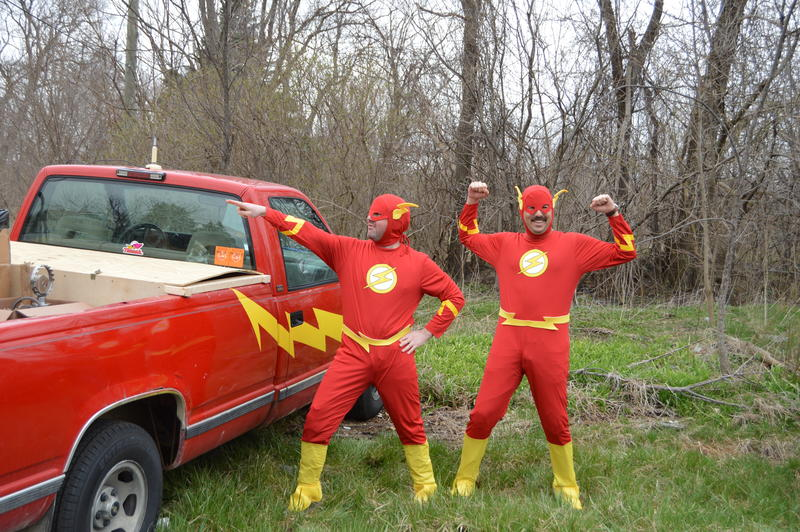 two men in flash suits standing by red truck with lightning bolt