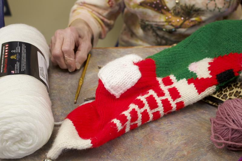 A volunteer fixes a hole in a knitted Christmas stocking