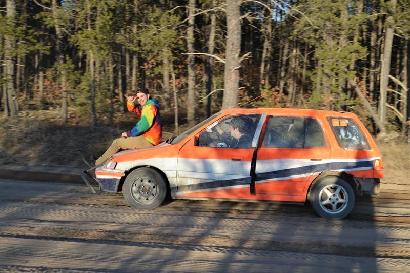 man on hood of orange car