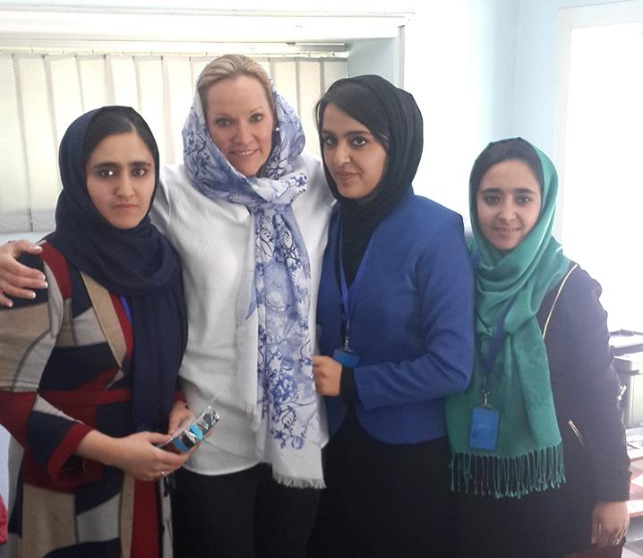 Three women pose with Lori Blaker in Afghanistan