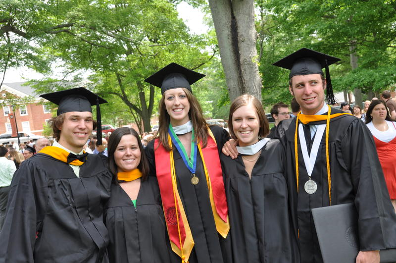 Group of five people in graduation cap and gown