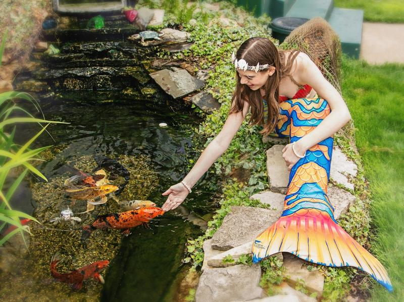 Lily Holshoe in her Mermaid Nadie costume touching a fish