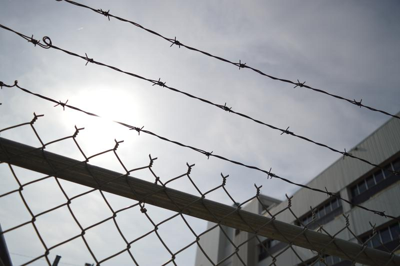 A chain-link fence and barbed wire