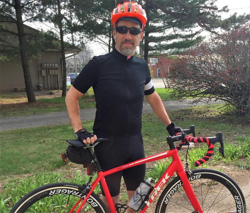 Man in bike gear standing with bike