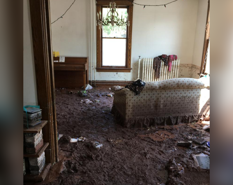 A living room, with a couch and a window, is shown with inches of mud piled on the carpet.
