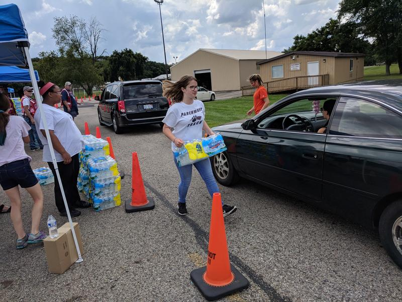 Volunteers pass out cases of bottled water at Parchment High School.