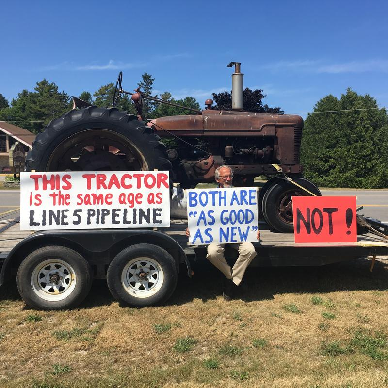 "A man sits in front of an old tractor. Signs read ""This tractor is the same age as the Line 5 pipeline. Both are as good as new. Not"""