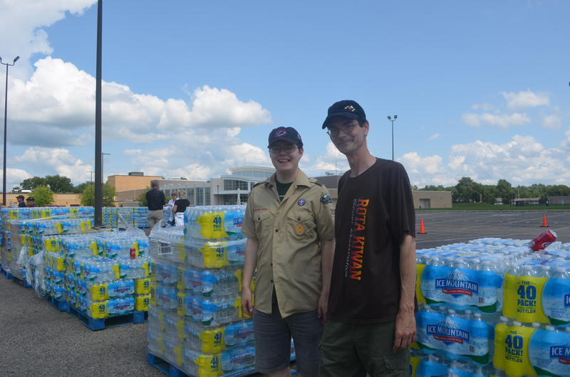 chase and steve moskalik in front of cases of bottled water at Parchment high school