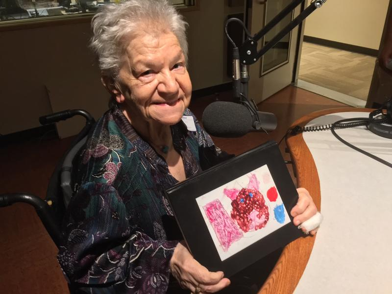 Joanne Savas in the studio holding a piece of a child's artwork
