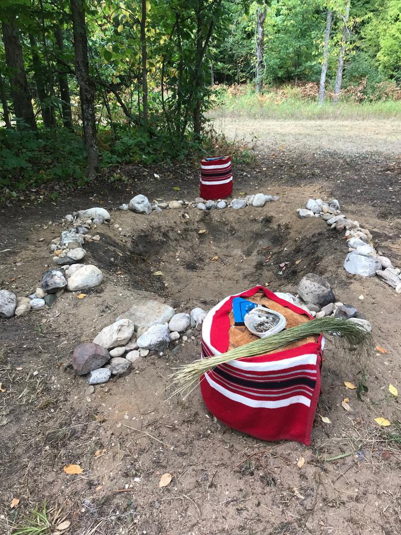 A fire pit surrounded with rocks, adjacent to a small stump with a colorful tapestry draped over it and sweetgrass and a seashell placed on top.