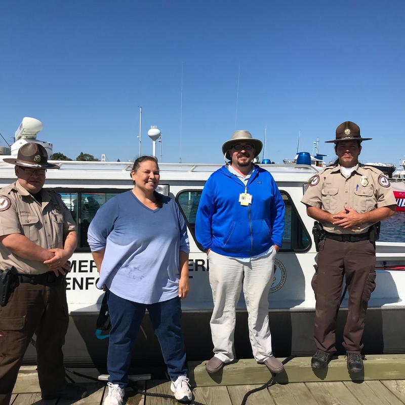 Two conservation officers and two others stand in front of a docked boat.