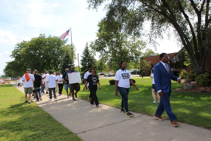 Protesters marching in front of the Westland Police Station