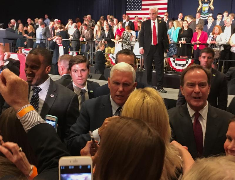 Republican Senate candidate John James (left) and gubernatorial candidate Bill Schuette (right) stand alongside Vice President Mike Pence at a GOP rally in Grand Rapids