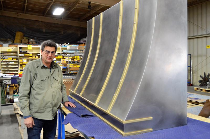 Steven Mark Fidler of Fidler Furniture Company standing next to a large cooking hood being built in his shop.
