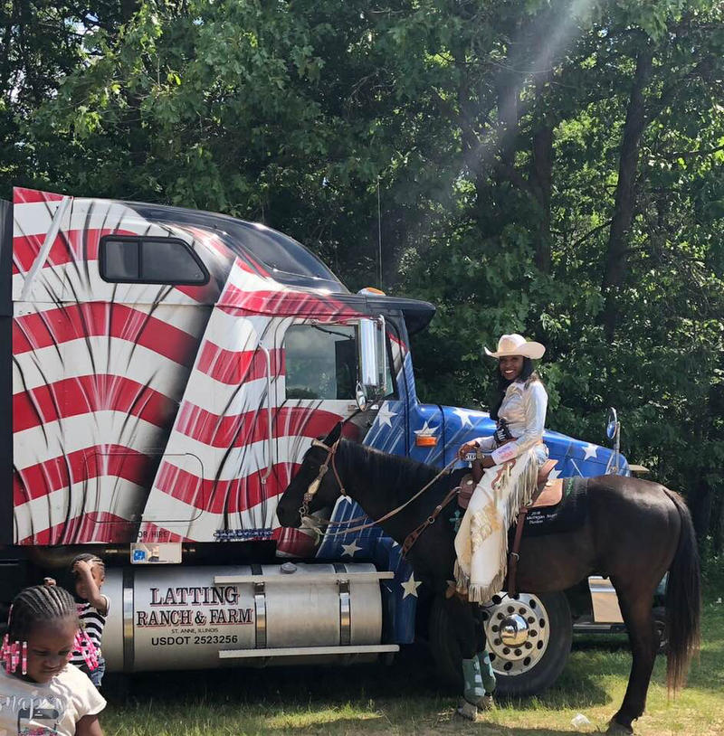 A Stars and Stripes truck cab and woman on a horse