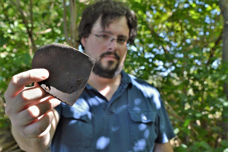 MLive reporter Garret Ellison holds a shoe heel found amongst leather strips on the bank of the Rogue River. Wolverine used a waterproofing formula which included a PFAS chemical.