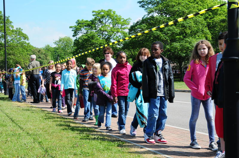 children lined up on a sidewalk