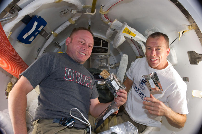 Image shows astronauts Andrew Feustel (right) and Mike Fincke (left) eating STEM bars for breakfast onboard the International Space Station.