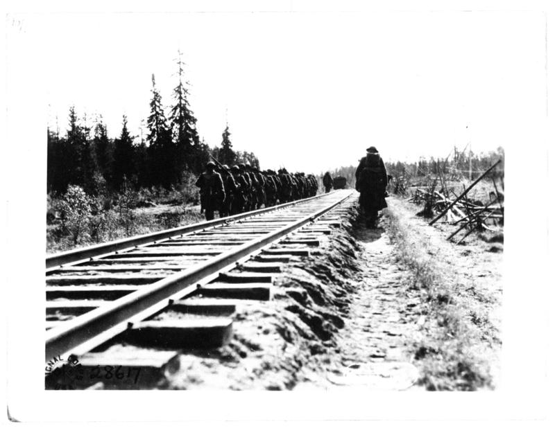 Company M, 339th Inf. after resting an hour, following the 17 hours march through the woods and swamps, set out again for the front.  They are seen in this picture starting out along the railroad line.