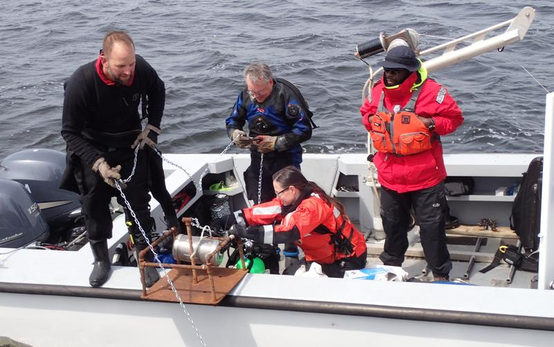 NOAA diver Beau Braymer (left) prepares to lower a mooring mounted with water quality monitoring equipment at a location in Lake Michigan near Muskegon.