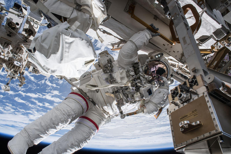 Image shows astronaut Andrew Feustel outside of the International Space Station floating above the Earth.