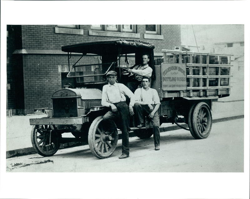 Three men posing next to the Feigenson family's truck, which they used to distribute Faygo products.