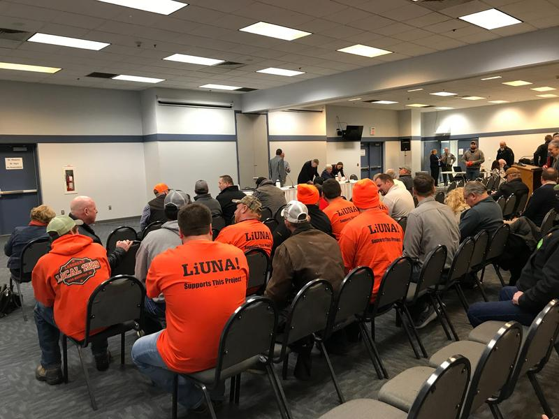 Rows of men in orange union t-shirts sit in a large meeting room filled with chairs.