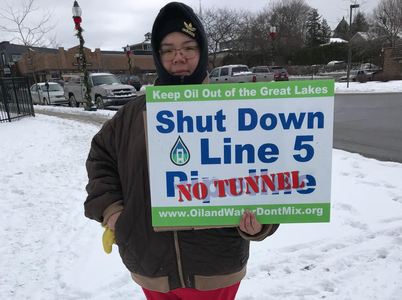 "A woman wearing warm clothing holds a sign that says ""Shut Down Line 5, No Tunnel""."