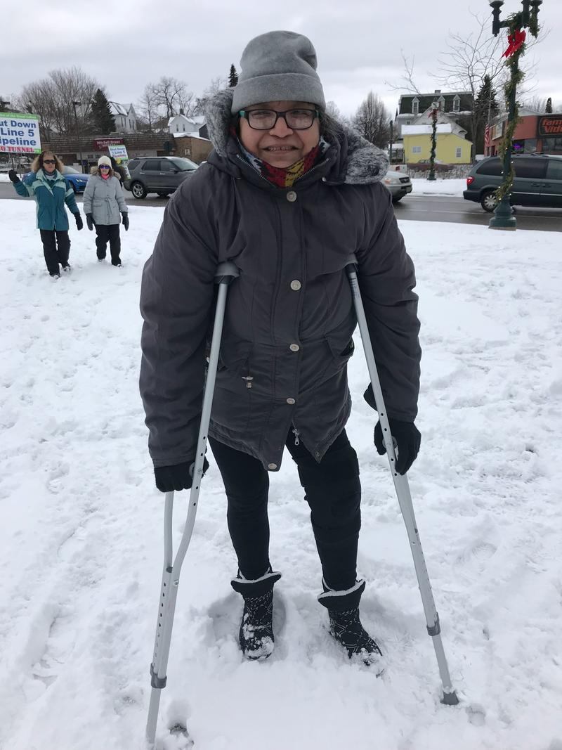 A woman in a puffy coat stands outside, against a snowy landscape, on crutches.