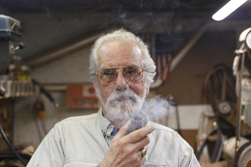 Lee Erck smokes his pipe in the basement of his home just outside Marquette.