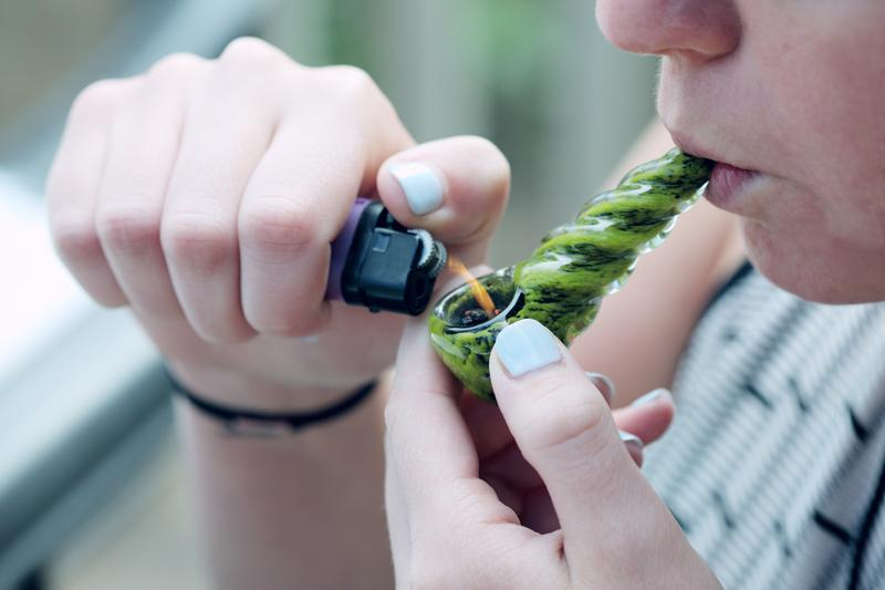 person smoking a marijuana pipe
