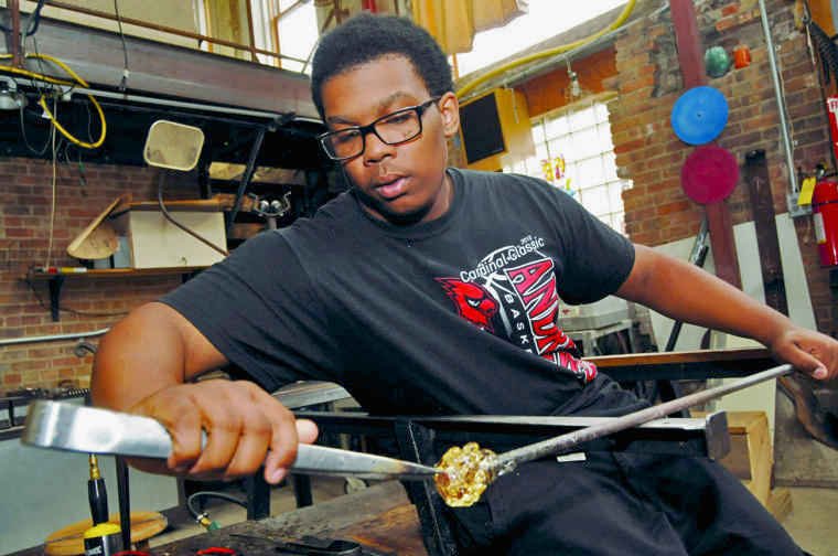 Otis Cornelius works on a piece of glass