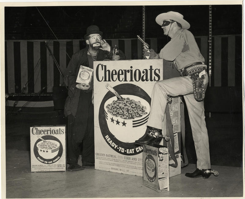 View of actor Brace Beemer, dressed as Lone Ranger, posing with clown and facsimile boxes of Cheerioats cereal