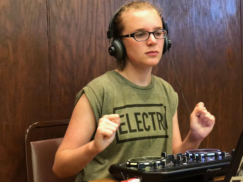 Maddie sitting in front of a DJ board