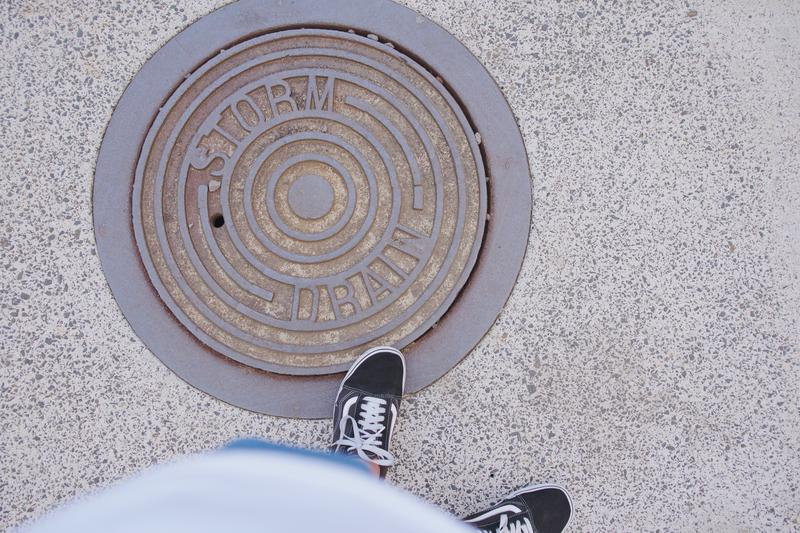 persons feet next to a manhole cover that reads
