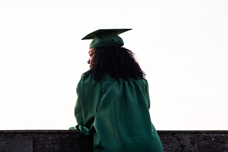 woman with curly hair in green graduation cap and gown looking over wall