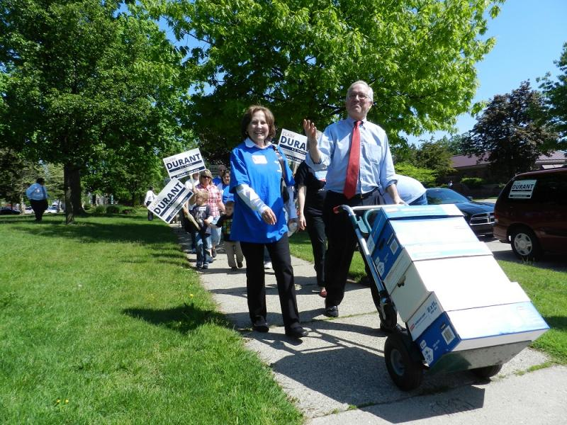 GOP U.S. Senate candidate Clark Durant is followed down the street by his suporters,  as he pushes boxes containing thousands of petition signatures to the Michigan Secretary of State's Office