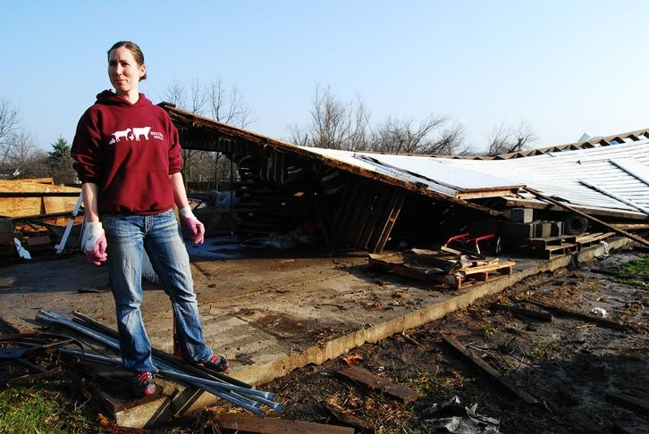Keri Romine, co-owner of Dexter Mill stands next to a structure damaged by the tornado that hit Thursday afternoon.