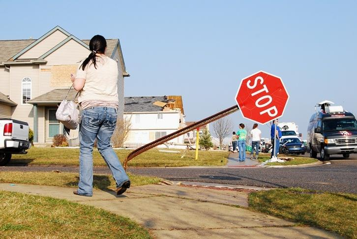 A woman walks by a stop sign bent from the tornado that hit Dexter on Thursday afternoon.