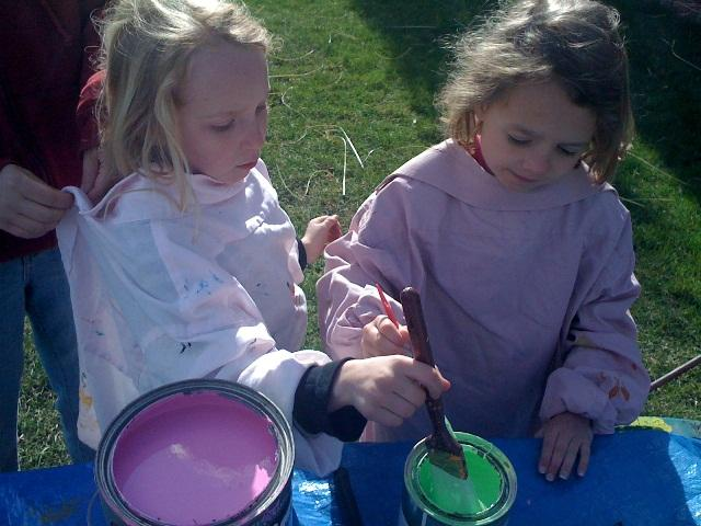 7-year old Ava (left) and her friend paint a banner at the makeshift art studio