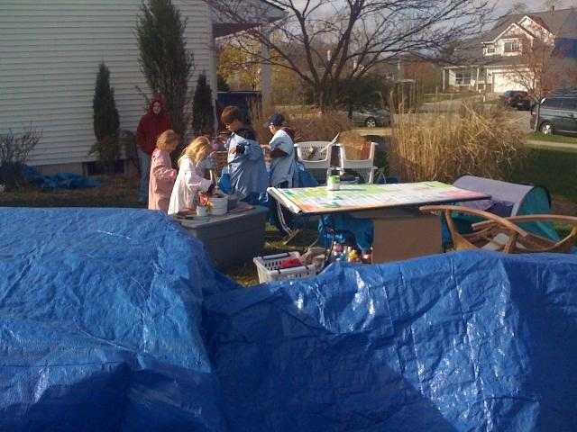 The makeshift outdoor studio; tarps cover the kids' art work and supplies