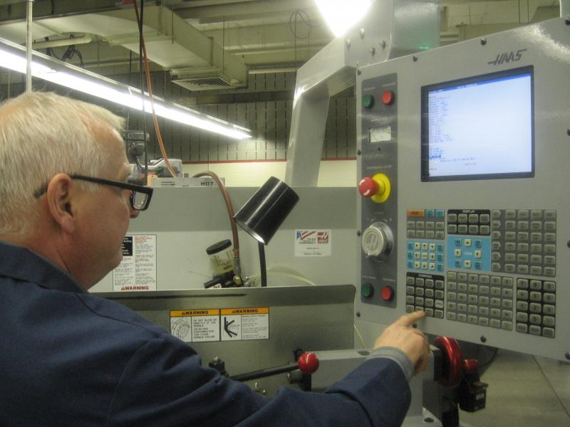 Instructor Steve Henkelman programs a CNC machine at Grand Rapids Community College.