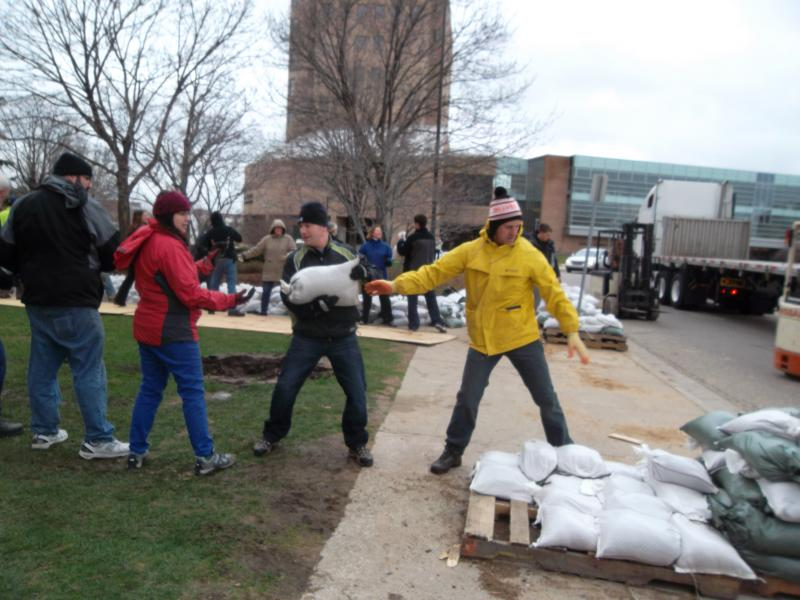 The Grand River is expected to crest at a record breaking 22.7 feet early next week. People help sand bag on Friday.