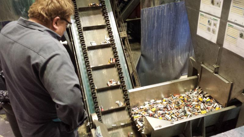 A worker studies the conveyor belt. If a lithium ion battery gets in, it could be dangerous.