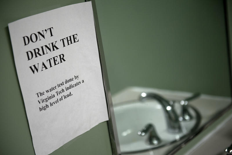 Sink in Flint with a warning sign.